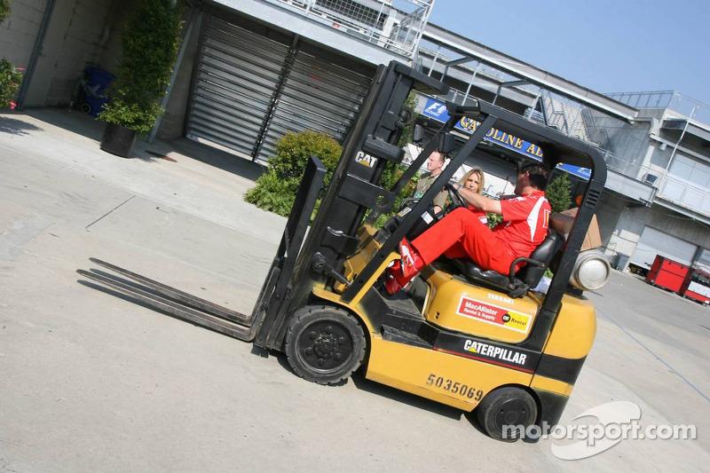 Un membre de l'équipe Ferrari conduit un chariot élévateur dans la voie des stands