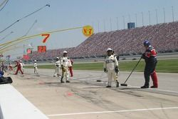 NASCAR officials keep an eye out for crew members sweeping up lug nuts