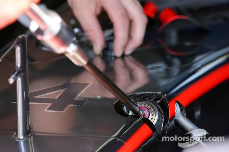 Un mécanicien remplace une longue partie ronde, probablement liée à la suspension de la McLaren MP4-21