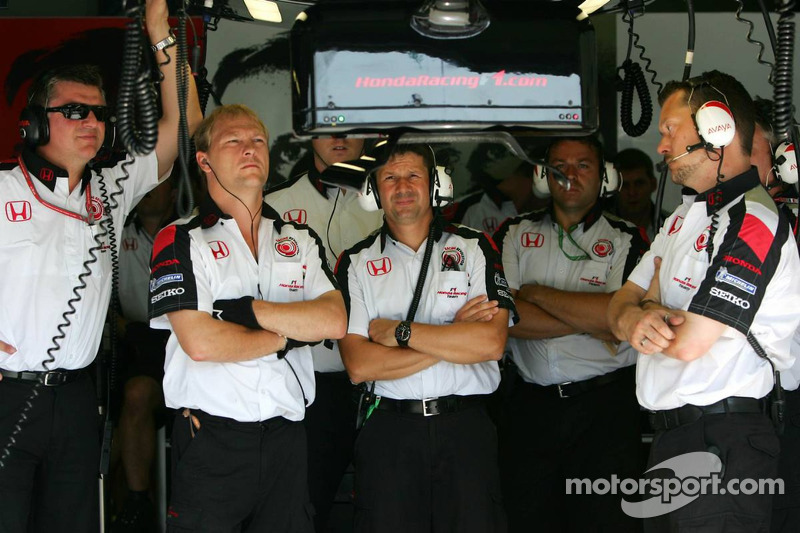 Des mécaniciens de Honda Racing regardent la course sur un écran TV