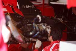 Des mécaniciens réparent les dommages après le feu sur la voiture de Michael Schumacher
