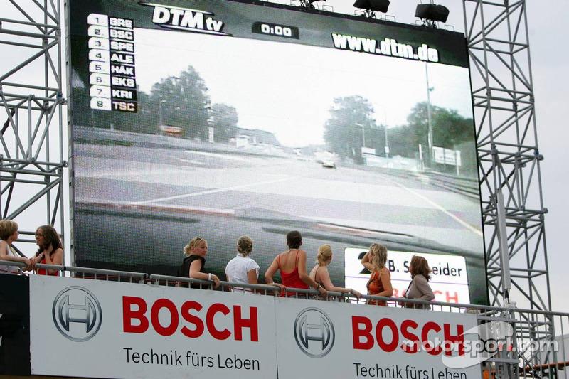 Des jeunes femmes regardent les qualification sur un écran géant depuis le haut des stands
