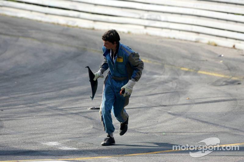 Un commissaire de course nettoie les débris sur la piste