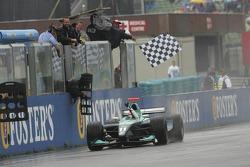 Nelson A. Piquet passe le drapeau à damier pour gagner la course