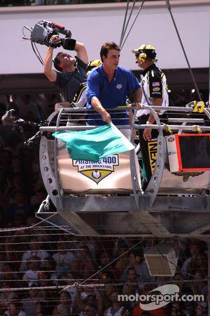 L'acteur Chris North agite le drapeau vert pour le début de la course