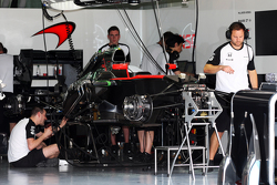 The McLaren MP4-30 is prepared in the pit garage