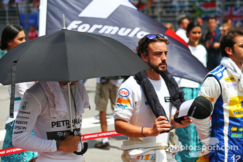 Lewis Hamilton, Mercedes AMG F1, dan Fernando Alonso, McLaren as the grid observes the national anthem