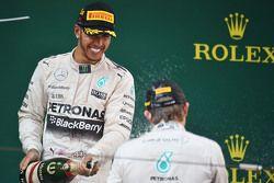 Победитель гонки Льюис Хэмилтон Mercedes AMG F1 празднует на подиуме с Нико Росбергом Mercedes AMG F