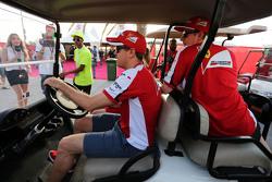 塞巴斯蒂安·维特尔, 法拉利,驾驶一辆高尔夫车,搭载了基米·莱库宁, 法拉利,和Britta Roeske, 法拉利新闻官