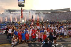Les enfants de pilotes et les membres de l'équipe se réunissent pour chanter l'hymne national