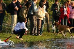 Собака убегает с шапкой Тома Кристенсена, которую он потерял упав в воду