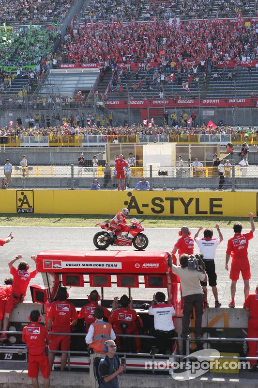 Los miembros del equipo Ducati celebran con Loris Capirossi cruza la línea de meta