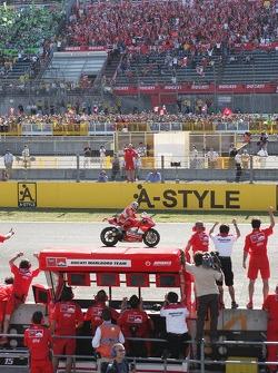 Ducati team members celebrate as Loris Capirossi crosses the finish line