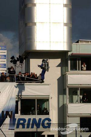 Un homme volant prend la bouteille de champagne pour le vainqueur sur le podium