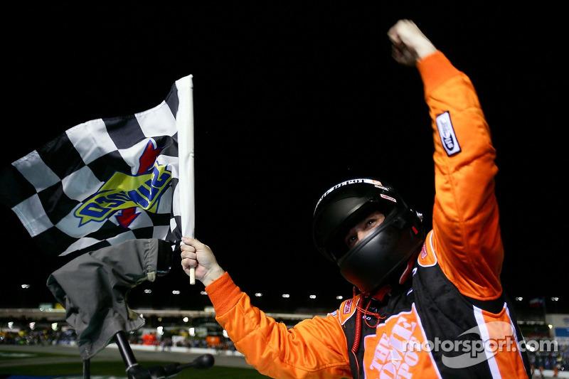 Le vainqueur de la course Tony Stewart savoure avec le drapeau après avoir escaladé la barrière