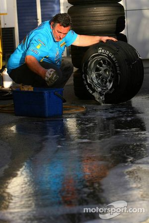 A Renault F1 Team mechanic cleans the Bridgestone tyres