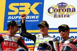 Troy Bayliss second, James Toseland premier et Noriyuki Haga sur le podium devant la foule