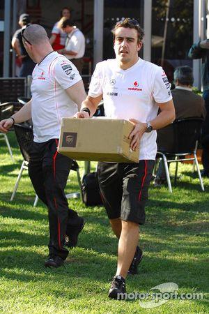 Fernando Alonso portant une boîte