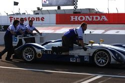 Dyson Racing team members push the Porsche RS Spyder back to the paddock