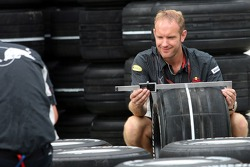A Red Bull Racing crew member checks the tires