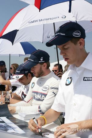 Sebastian Vettel and Nick Heidfeld sign autographs