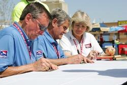 Johnny Rutherford et Al Unser Sr. signent une bannière