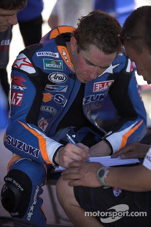 Tommy Haden describes his Suzuki's handling to crew members after a practice session