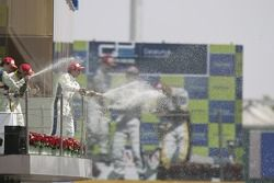 Timo Glock celebrates on the podium with Javier Villa and Lucas di Grassi