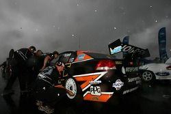 L'équipe Tasman Motorsport travaille sur la voiture pendant que la pluie tombe fortement