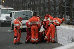 Safety crew members check the damage after Josef Newgarden's crash