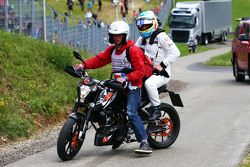 Race retiree Fernando Alonso, McLaren returns to the pits on a motorbike