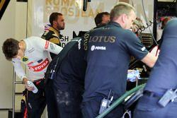 Romain Grosjean, de Lotus F1 Team ayuda a limpiar su Lotus F1 E23 después de caer en la trampa de gr