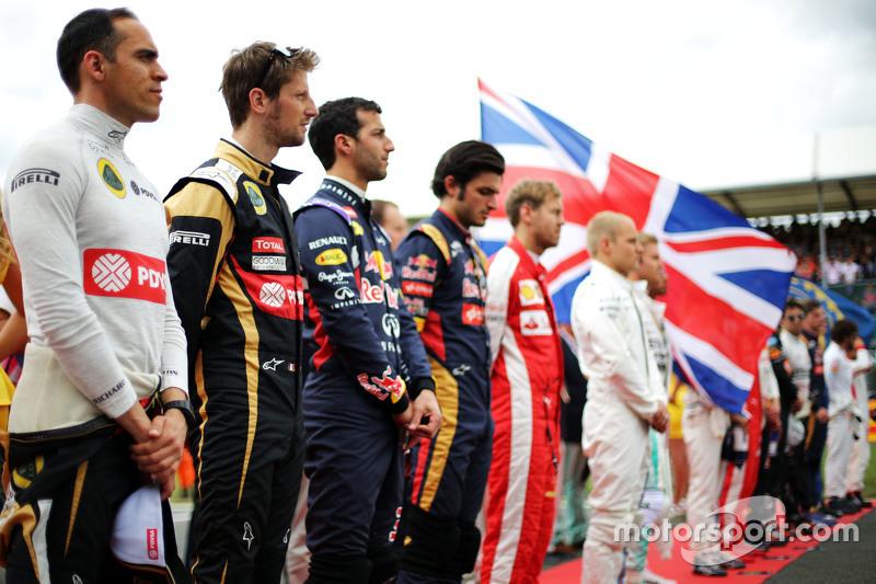 Pastor Maldonado, Lotus F1 Team, dan Romain Grosjean, Lotus F1 Team as the grid observes the nationa