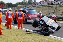 Oficiales de seguridad atienden al accidentado Sahara Force India de Sergio Pérez.