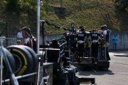 Status Grand Prix mechanics travel to the pit lane