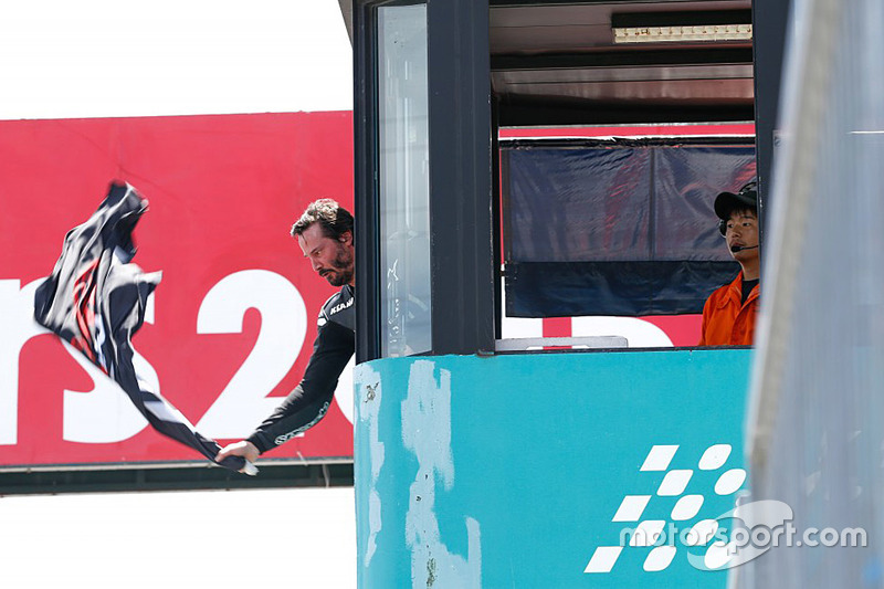 Keanu Reeves waves the flag to start the race