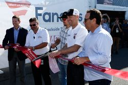 Martin Truex Jr. and Kevin Harvick cup the ribbon to officially open the NASCAR Trackside Superstore