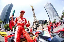 Esteban Gutiérrez con una bandera de México festeja en la columna del Angel de la Independencia durante Scuderia Ferrari Street Demo en la Ciudad de México