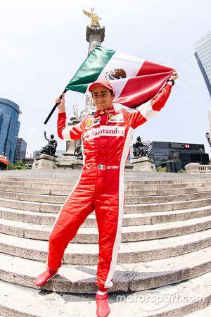 Esteban Gutiérrez con una bandera de México festeja en la columna del Angel de la Independencia dura