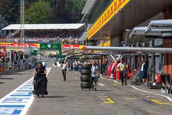 Lotus F1 Team and Williams mechanics walk down the pit lane