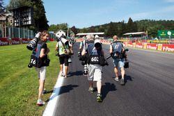 Фотографы идут к повороту Ля-Сурс перед началом гонки