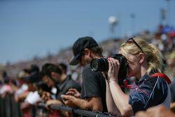 Фотограф на трибуне снимает гонку на треке