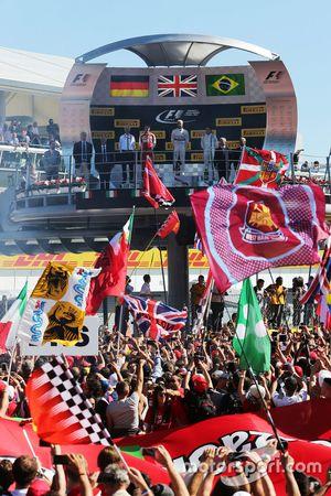 Подиум: второе место - Себастьян Феттель, Ferrari празднует ; победитель гонки - Льюис Хэмилтон; и т