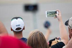Les fans filment la course dans les tribunes