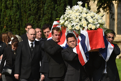Mark Webber and Dario Franchitti help carry the casket of Justin Wilson during funeral proceedings