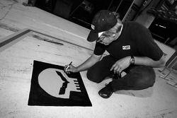 Membre de l'équipe Corvette Racing signe le logo C6.R sur la voie des stands