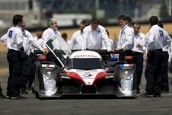 Membres du Team Peugeot Total poussant la voiture pour la photo d'équipe