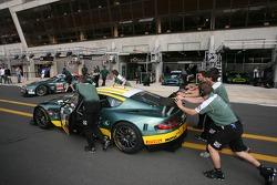 Membres de l'équipe Aston Martin Racing poussant leur voiture sur la voie des stands