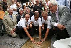 Les vainqueurs des 24 Heures du Mans 2006 Marco Werner, Frank Biela et Emanuele Pirro mettent leurs mains sur la plaque d'égout traditionnels des gagnants au centre-ville du Mans