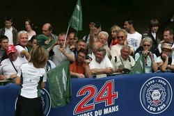 Membre de l'équipe Aston Martin Racing donne drapeaux pour les fans